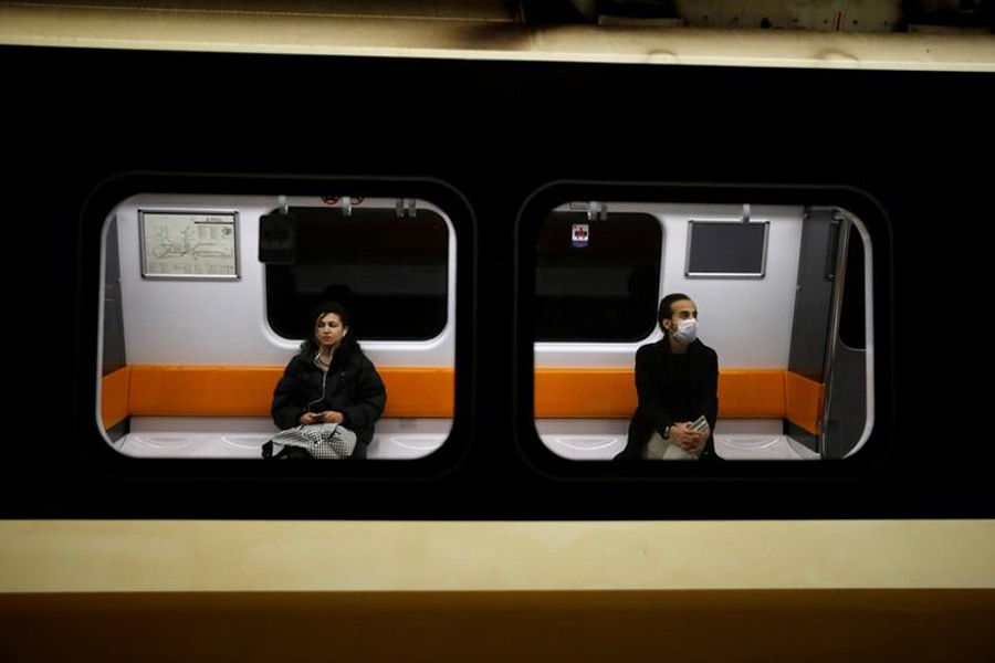 A man wearing a protective face mask and a woman are seen on a train as the spread of the coronavirus disease (COVID-19) continues in Istanbul, Turkey on March 26, 2020 — Reuters/Files