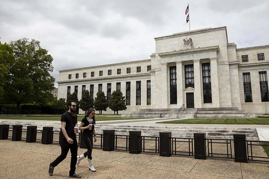 People walk past the U.S. Federal Reserve building in Washington D.C., the United States, May 21, 2020. (Photo by Ting Shen/Xinhua)