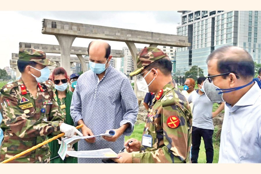 DNCC mayor Atiqul Islam and others looking at the map of the retention canal to be excavated during the mayor's visit to Kha Para, opposite Le Meridien hotel, in the city on Thursday — FE photo