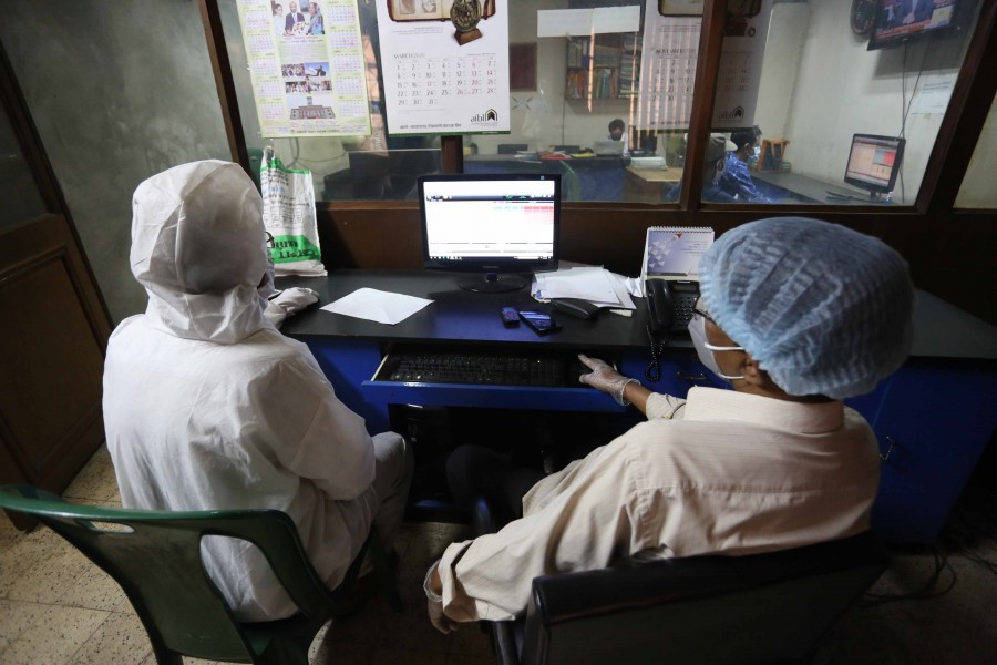 Investors wearing protective gears monitoring stock price movements on computer screens at a brockerage house in the capital city — FE photo