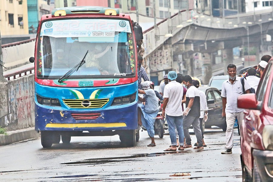 A bus picks up passengers from the middle of a road in Shantinagar area of the city on Thursday without maintaining any health safety guidelines amid coronavirus outbreak — FE photo by KAZ Sumon