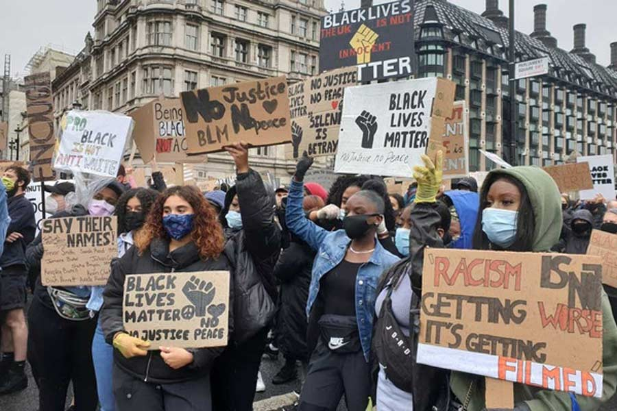 Demonstrators holding signs during a Black Lives Matter protest in Parliament Square, following the death of George Floyd who died in police custody in Minneapolis, in London, Britain on Saturday. –Reuters Photo