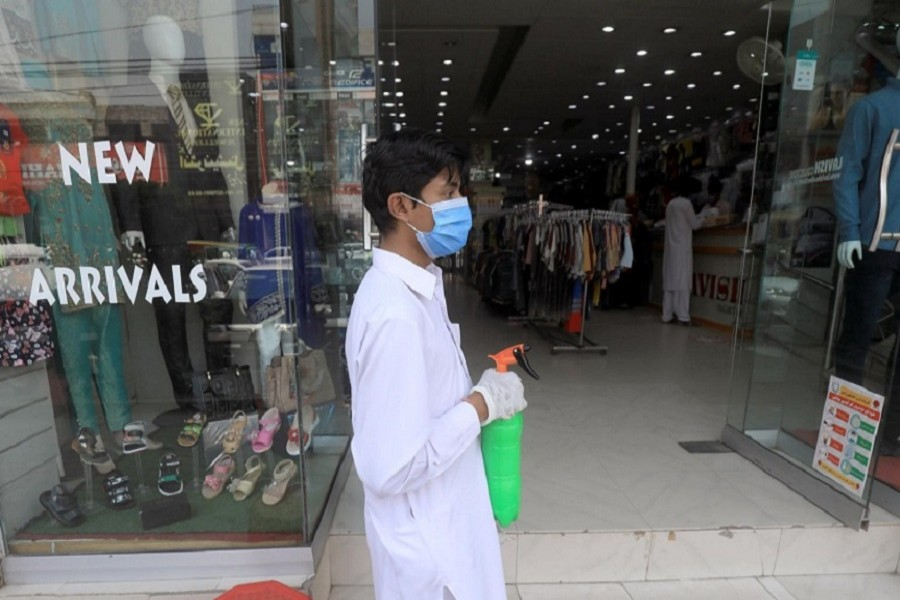 A worker wearing a protective face mask and gloves holds a spray bottle to disinfect customers outside a shop in a market, after Pakistan started easing lockdown as the coronavirus disease (COVID-19) continues, in Peshawar, Pakistan May 11, 2020. — Reuters/Files