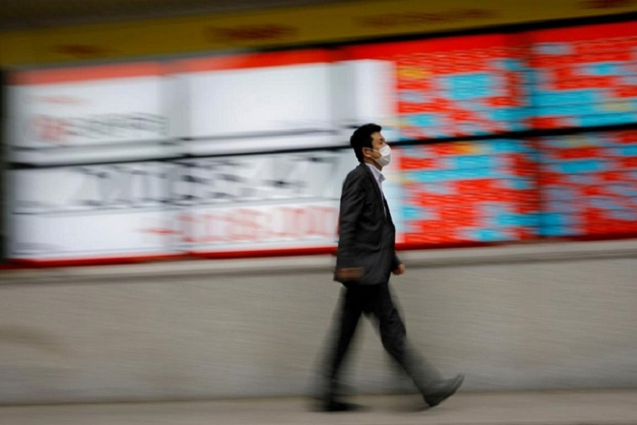 A man wearing a protective face mask, following the coronavirus disease (COVID-19) outbreak, walks in front of a stock quotation board outside a brokerage in Tokyo, Japan, May 18, 2020. — Reuters