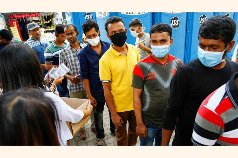 Migrant workers, mostly from Bangladesh, queue to collect free masks and get their temperatures taken in Singapore                  — Reuters