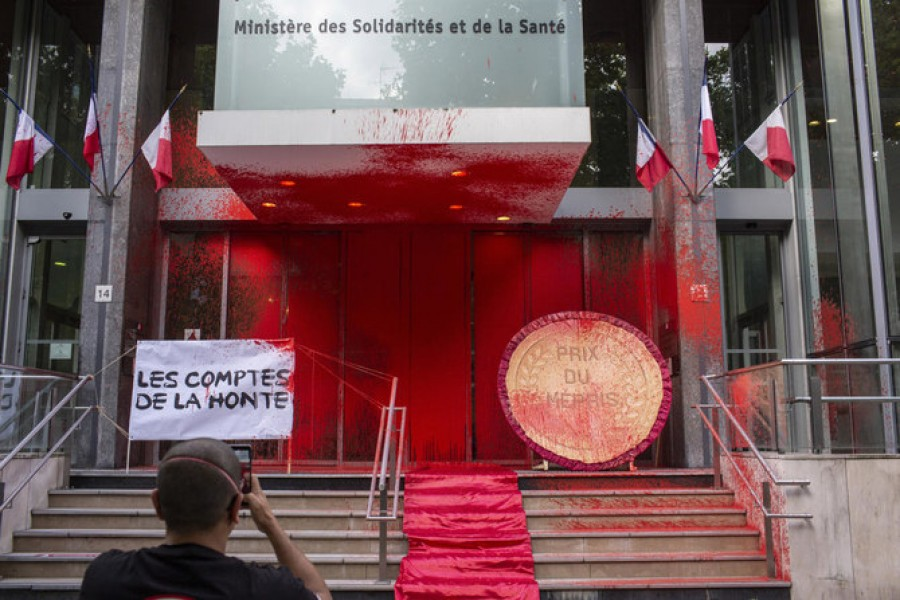 Activists deface the French health ministry building with red paint during a lighting protest on June 20, 2020. (AP)