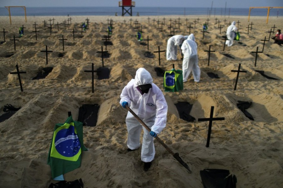 Activists of the NGO Rio de Paz wear protective gear to dig graves on Copacabana beach to symbolize the dead from coronavirus during a demonstration in Rio de Janeiro, Brazil — Reuters/Files