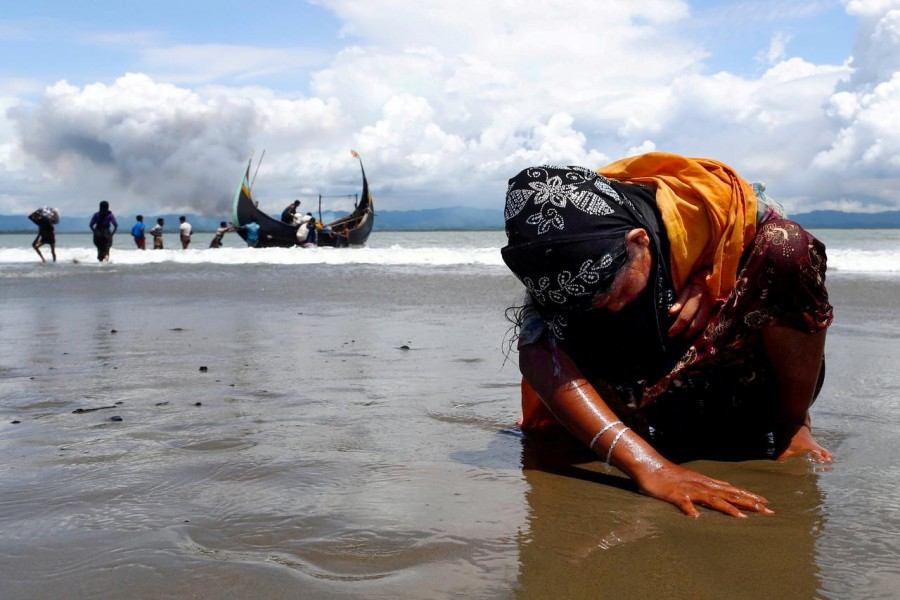 An exhausted Rohingya refugee woman touches the shore after crossing the Bangladesh-Myanmar border by boat through the Bay of Bengal in Shah Porir Dwip, Bangladesh on September 11, 2017 — Reuters/Files