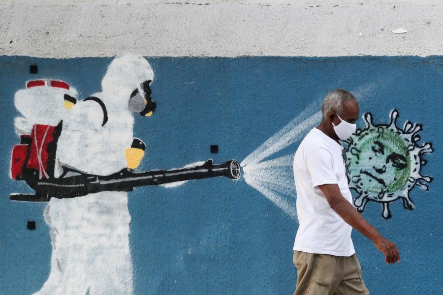 A man walks next to a graffiti depciting a cleaner wearing protective gear spraying viruses with the face of Brazil's President Jair Bolsonaro amid the coronavirus disease (Covid-19) outbreak, in Rio de Janeiro, Brazil on June 12, 2020 — Reuters/Files
