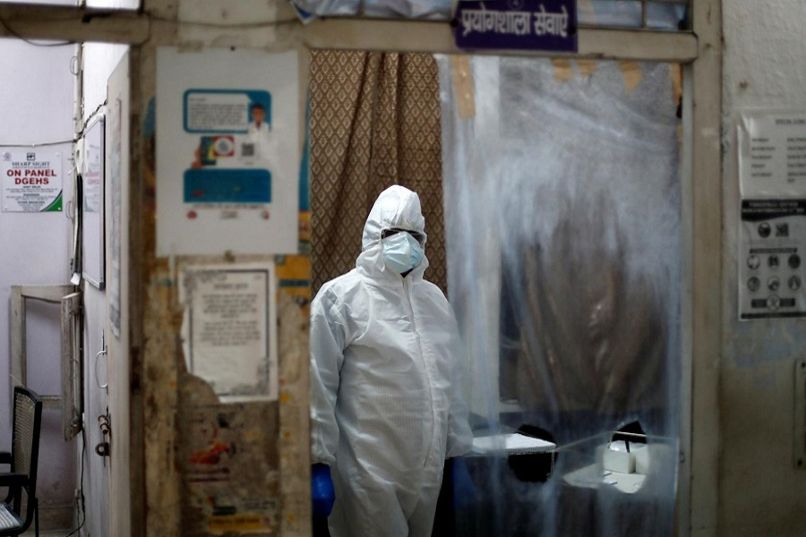 A health worker in personal protective equipment (PPE) waits for the next person to get tested for the coronavirus disease (COVID-19) at a local health centre, amid the spread of the disease, in New Delhi, India, June 27, 2020 – Reuters