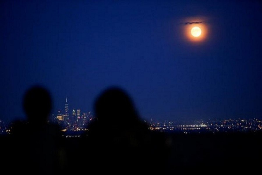 "People watch the full moon, known as the ""Buck Moon"", while it rises over the skyline of New York and One World Trade Center, as seen from West Orange, in New Jersey, US, July 16, 2019 – Reuters/Files"
