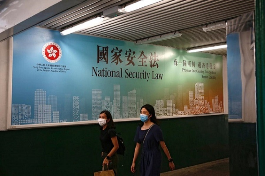 Women walk past a government-sponsored advertisement promoting the new national security law as a meeting on national security legislation takes place in Hong Kong, China, June 29, 2020 — Reuters