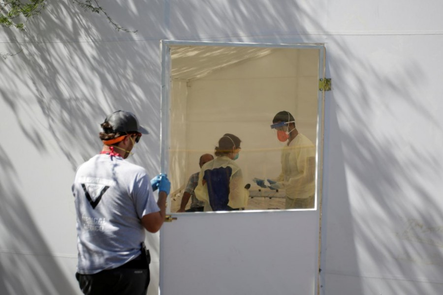 Medical staff from Global Response Management take samples from a patient suspected of contracting coronavirus disease (COVID-19) at an isolation area of a hospital installed at a migrant encampment, where more than 2,000 people live while seeking asylum in the U.S., in Matamoros, Mexico May 1, 2020. REUTERS/Daniel Becerril/File Photo