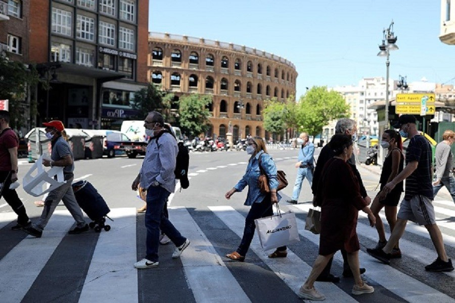 People wearing face masks walk on a crosswalk, as some Spanish provinces are allowed to ease lockdown restrictions during phase one, amid the coronavirus disease (Covid-19) outbreak, in Valencia, Spain May 19, 2020 — Reuters/Files