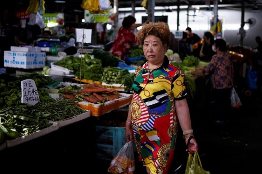 A woman carries vegetables and food at a market, following the coronavirus disease (Covid-19) outbreak, in Shanghai, China. June 09, 2020 — Reuters/Files