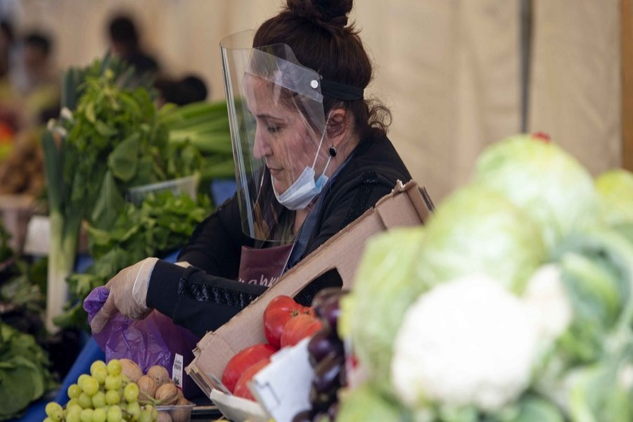 A street vendor wearing a face shield and gloves picks fruits for a customer at a street market in Moscow, Russia, on June 5, 2020. (Photo by Alexander Zemlianichenko Jr/Xinhua)