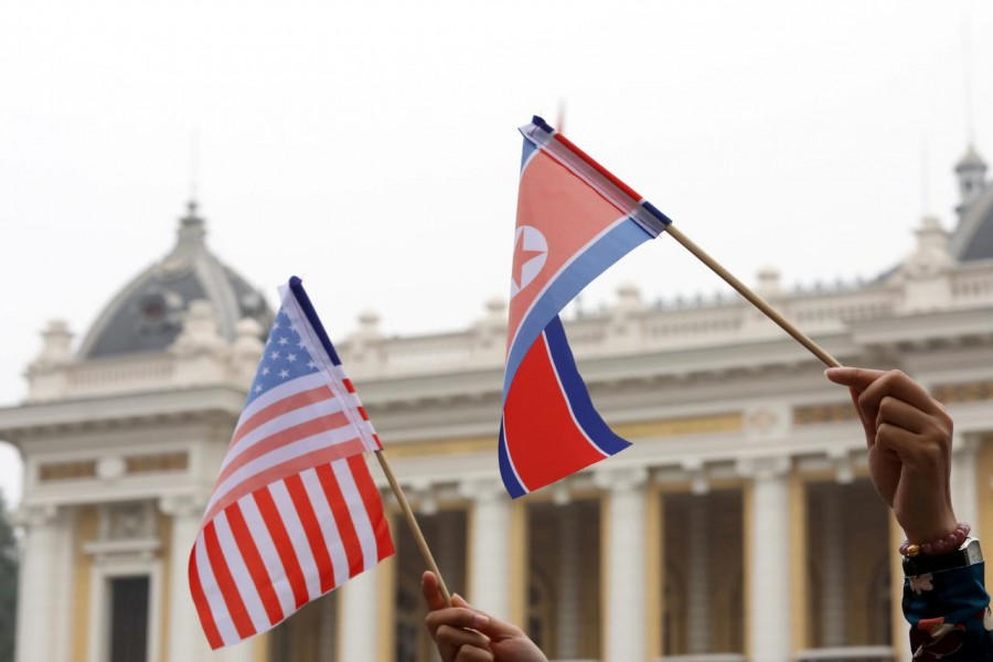 Residents hold US and North Korean flags while they wait for motorcade of North Korea's leader Kim Jong Un en route to the Metropole Hotel for the second US- North Korea summit in Hanoi, Vietnam February 28, 2019. REUTERS/Kham