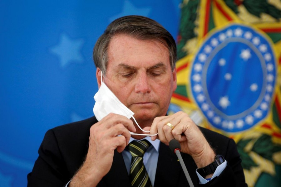 Brazil's President Jair Bolsonaro adjusts his protective face mask during a press statement to announce federal judiciary measures to curb the spread of the coronavirus disease (COVID-19) in Brasilia, Brazil March 18, 2020. Picture taken March 18, 2020. REUTERS/Adriano Machado