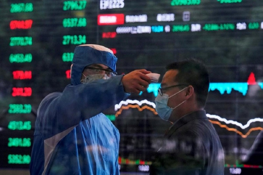 A worker wearing a protective suit takes body temperature measurement of a man inside the Shanghai Stock Exchange building, as the country is hit by the coronavirus outbreak, at the Pudong financial district in Shanghai, China, February 28, 2020 — Reuters/Files