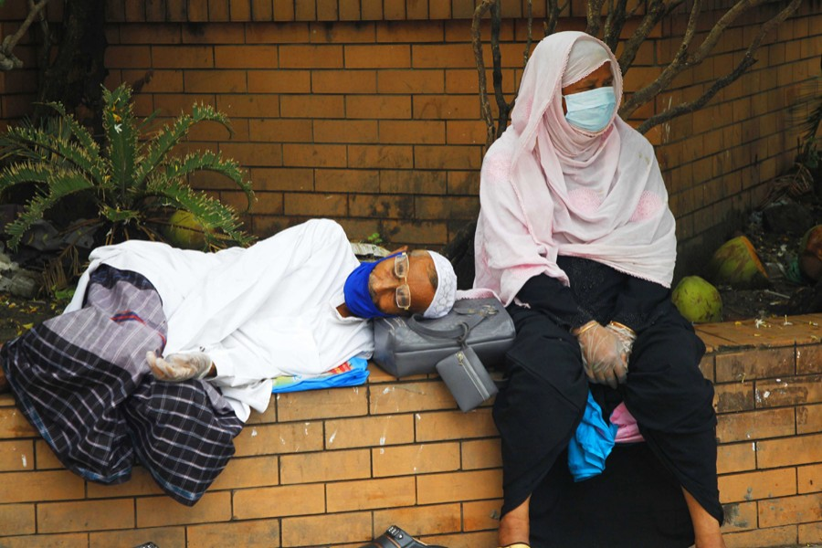 An elderly couple wearing protective masks and gloves rest outside Mugda General Hospital in the capital as they wait for Covid-19 test — File photo