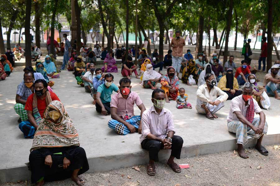 People waiting for relief supplies provided by local community in Dhaka a few months ago	—Al Jazeera Photo