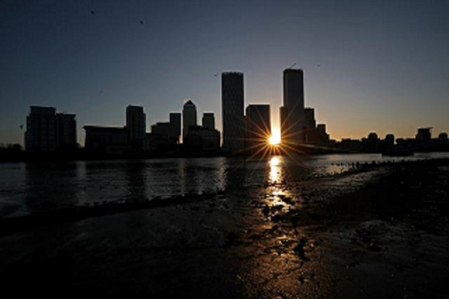 The sun rises behind the Canary Wharf financial district in London, Britain, February 12, 2020 — Reuters/Files