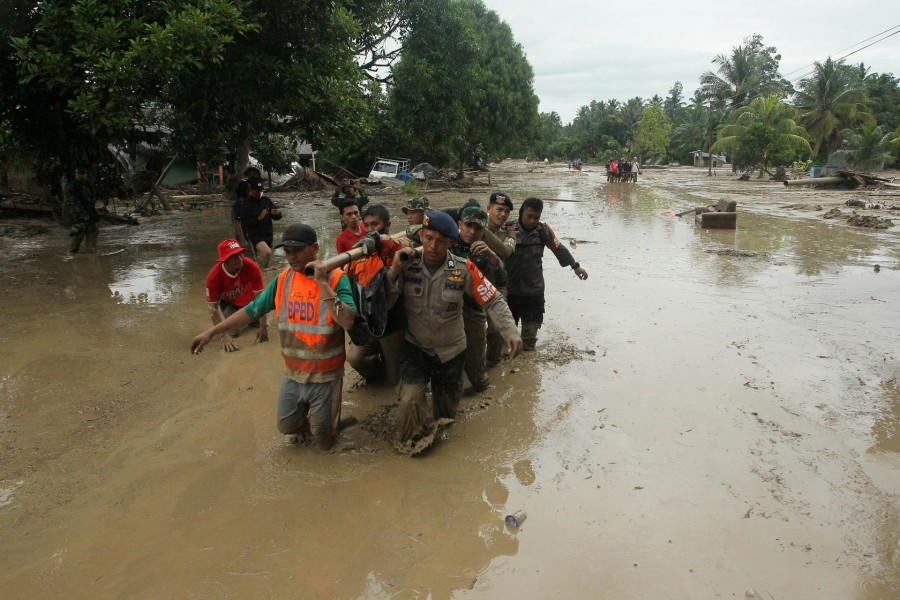Officers evacuate victims in Radda Village, following flash floods that left several dead and dozens remain missing, in North Luwu in Sulawesi, Indonesia July 14, 2020. Antara Foto/Indra/ via REUTERS