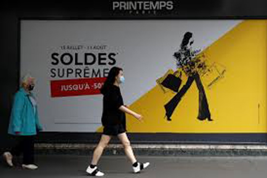 Women, wearing protective face masks, walk past the department store Le Printemps Haussmann decorated with a discount sign in Paris on the first day of summer sales following the outbreak of the coronavirus disease (COVID-19) in France, July 15, 2020. REUTERS/Gonzalo Fuentes