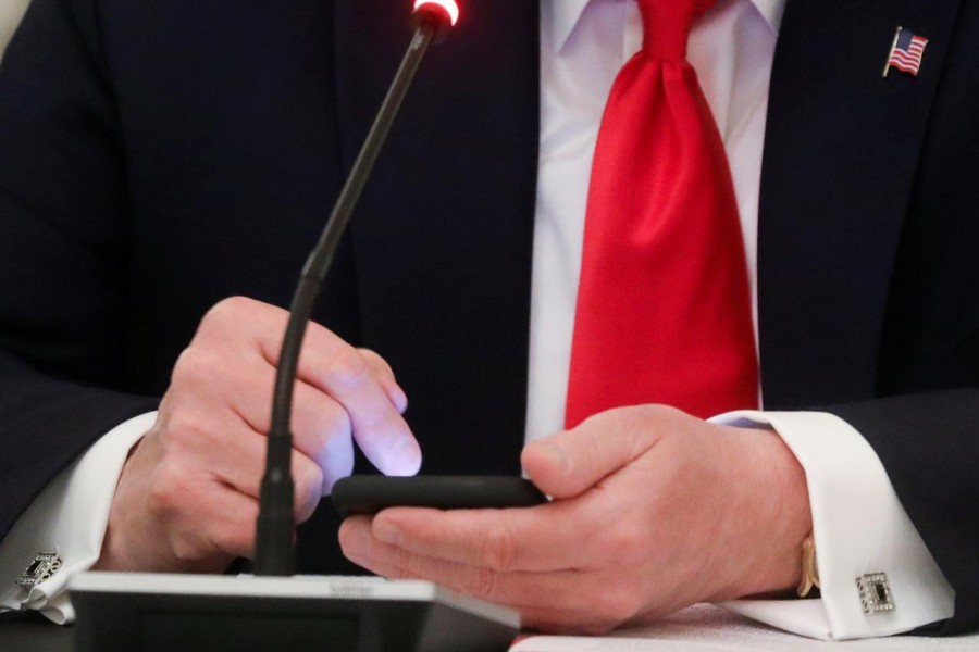 U.S. President Donald Trump taps the screen on a mobile phone at the approximate time a tweet was released from his Twitter account, during a roundtable discussion on the reopening of small businesses in the State Dining Room at the White House in Washington, US on June 18, 2020 — Reuters/Files