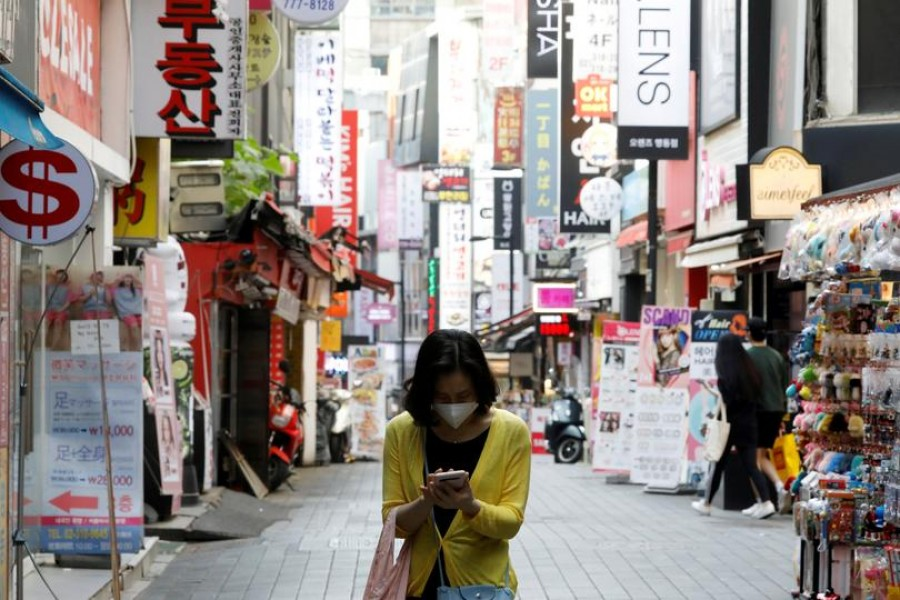 A woman wearing a mask looks at her mobile phone amid social distancing measures to avoid the spread of the novel coronavirus, in Myeongdong shopping district in Seoul, South Korea, May 28, 2020. REUTERS/Kim Hong-Ji//File Photo