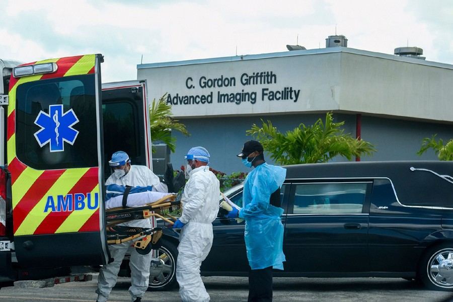 Emergency Medical Technicians (EMT) arrive with a patient while a funeral car begins to depart at North Shore Medical Center where the Covid-19 patients are treated, in Miami, Florida, US on July 14, 2020 — Reuters/Files