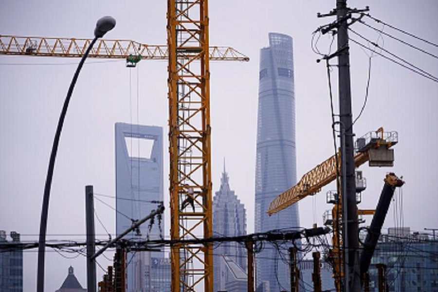 A worker is seen on a crane at a construction site in front of Lujiazui financial district, following the coronavirus disease (Covid-19) outbreak, in Shanghai, China, July 16, 2020 — Reuters