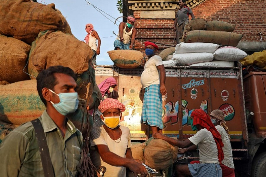 Labourers wearing protective face masks load grocery items onto a supply truck at a wholesale market during the coronavirus disease (Covid-19) outbreak in Kolkata, July 24, 2020 — Reuters