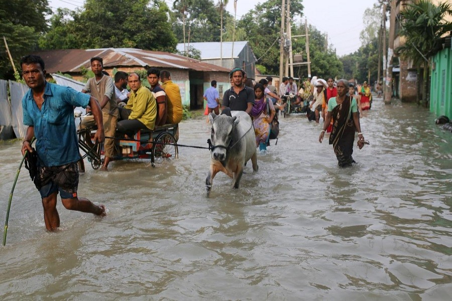 People move along a flooded road in Gaibandha, Bangladesh, July 18, 2019 — Reuters/Files