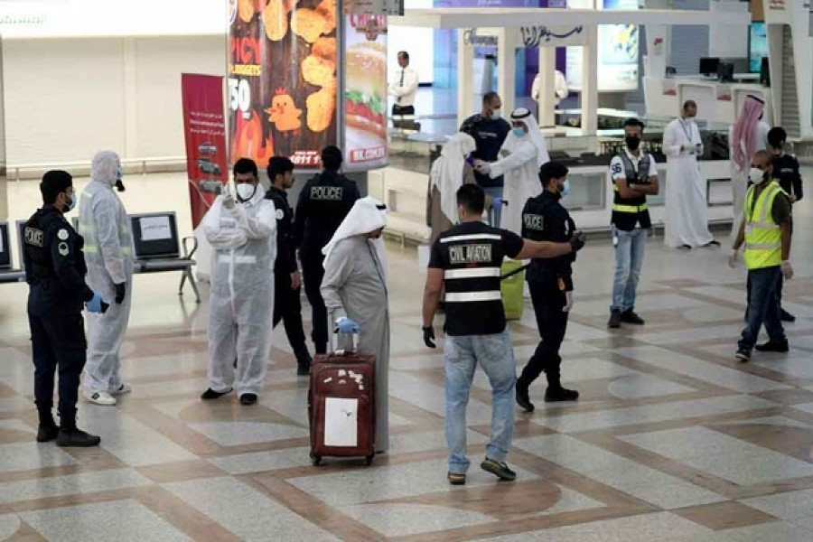 A Kuwaiti passenger holding his luggage walks by the police and civil aviation personnel upon his arrival from Amman at Kuwait Airport, following the outbreak of the coronavirus disease (Covid-19), in Kuwait City, Kuwait, April 21, 2020 — Reuters