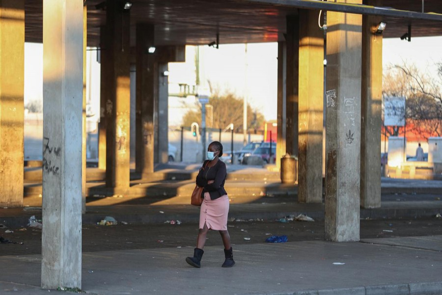 FILE PHOTO: A Stranded commuter walks at a deserted Baragwanath taxi rank during a protest by the South African minibus taxi operators against the government's financial relief package to the taxi industry, during the coronavirus disease (COVID-19) lockdown, in Soweto, South Africa, June 22, 2020. REUTERS/Siphiwe Sibeko