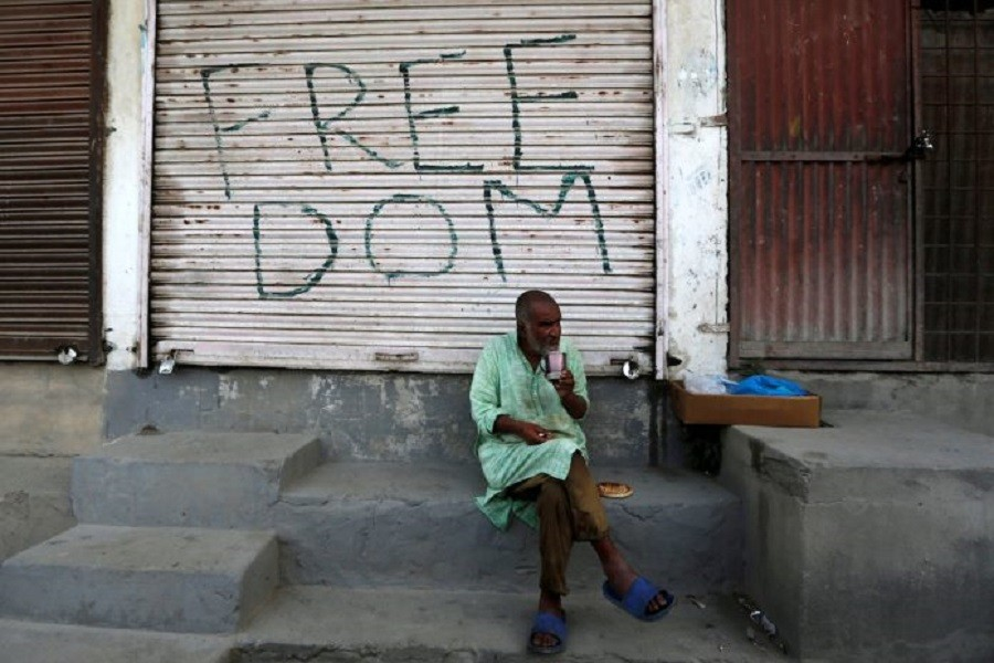A Kashmiri man drinks tea in front of a closed shop painted with graffiti in Anchar neighbourhood in Srinagar July 28, 2020 — Reuters