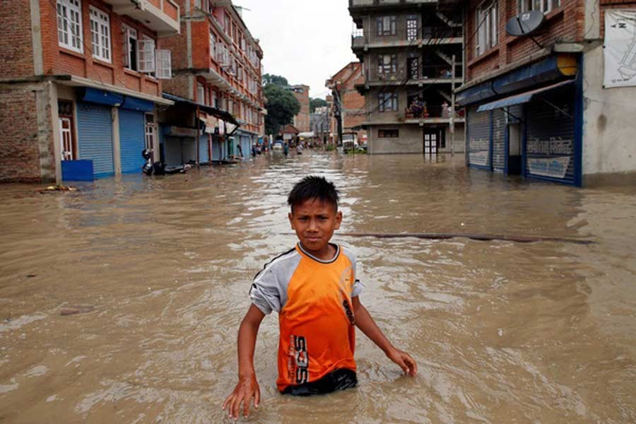 A boy walking along the flooded neighbourhood after incessant rainfall in Nepal last month –Reuters Photo