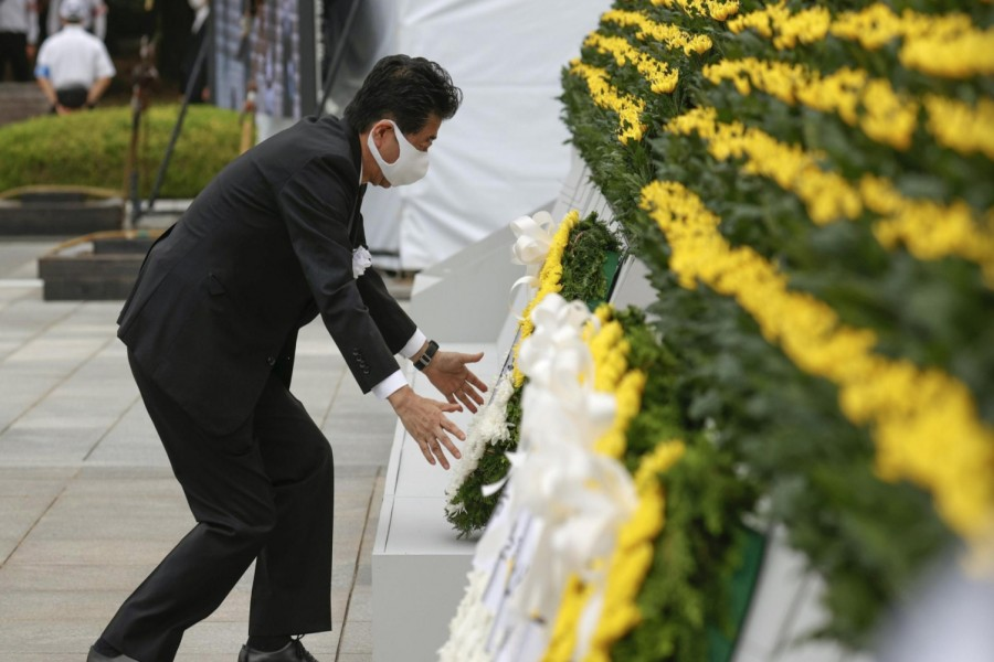 Japan's Prime Minister Shinzo Abe wearing a protective face mask, offers a wreath to the cenotaph for the victims of the 1945 atomic bombing, at Peace Memorial Park in Hiroshima, western Japan, August 6, 2020, on the 75th anniversary of the atomic bombing of the city. Mandatory credit Kyodo/via REUTERS