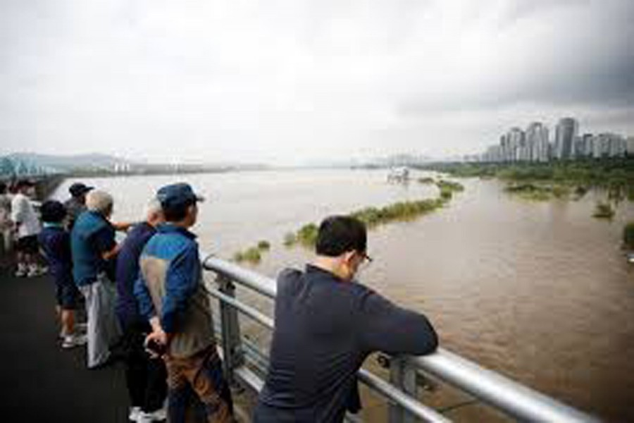 Residents look on a submerged Han River park by flooded Han River in Seoul, South Korea, August 06, 2020. REUTERS/Kim Hong-Ji