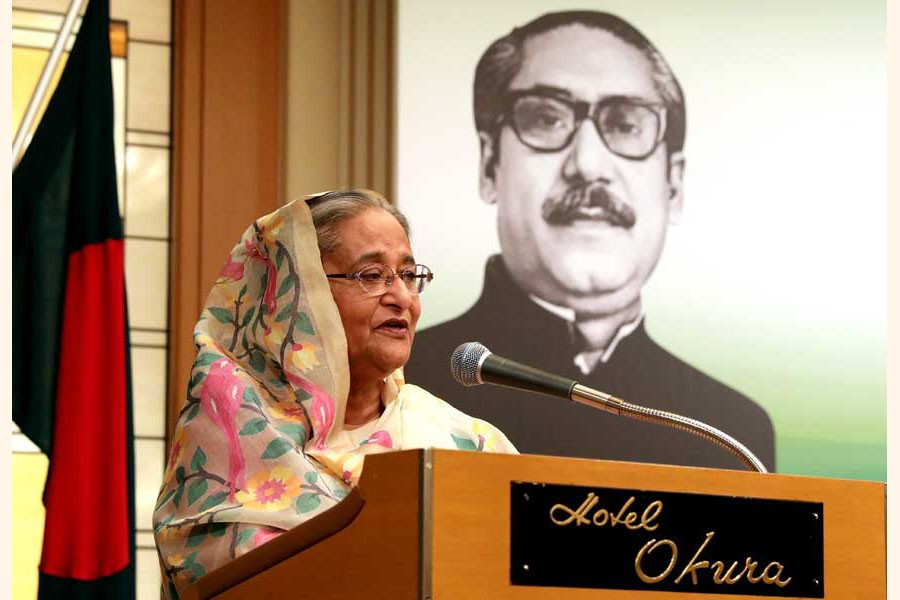 Prime Minister Sheikh Hasina at a reception in Japan last year with the portrait of Father of the Nation  Bangabandhu Sheikh Mujibur Rahman in the background 	— Website of Bangladesh Awami League