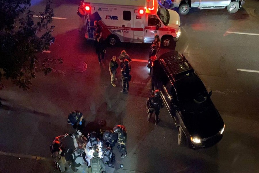 Medics and police personnel (bottom) surround the victim of a shooting in Portland, Oregon, U.S. August 29, 2020, in this still image obtained from a social media video. Courtesy of Sergio Olmos/Social Media via REUTERS.
