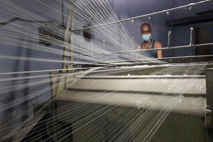 A worker wearing a protective face mask works on a loom in a textile factory, amidst the coronavirus disease (COVID-19) outbreak, in Meerut, India, July 7, 2020. REUTERS/Manoj Kumar/File Photo