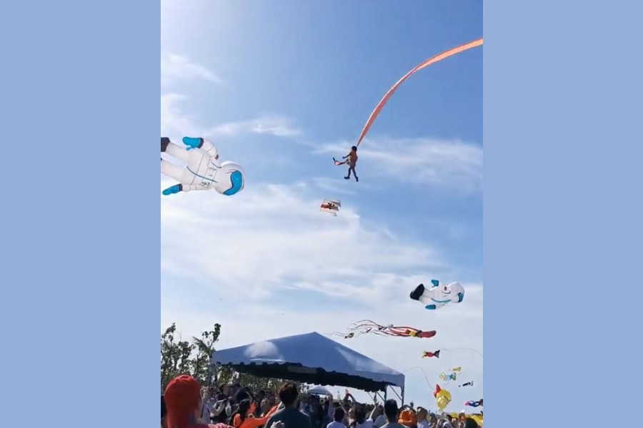 A child is pulled up in the air by a kite at an International Kite Flying Festival, in Hsinchu, Taiwan August 30, 2020 in this screen grab obtained from a social media video. Facebook @viasblog.tw/via REUTERS