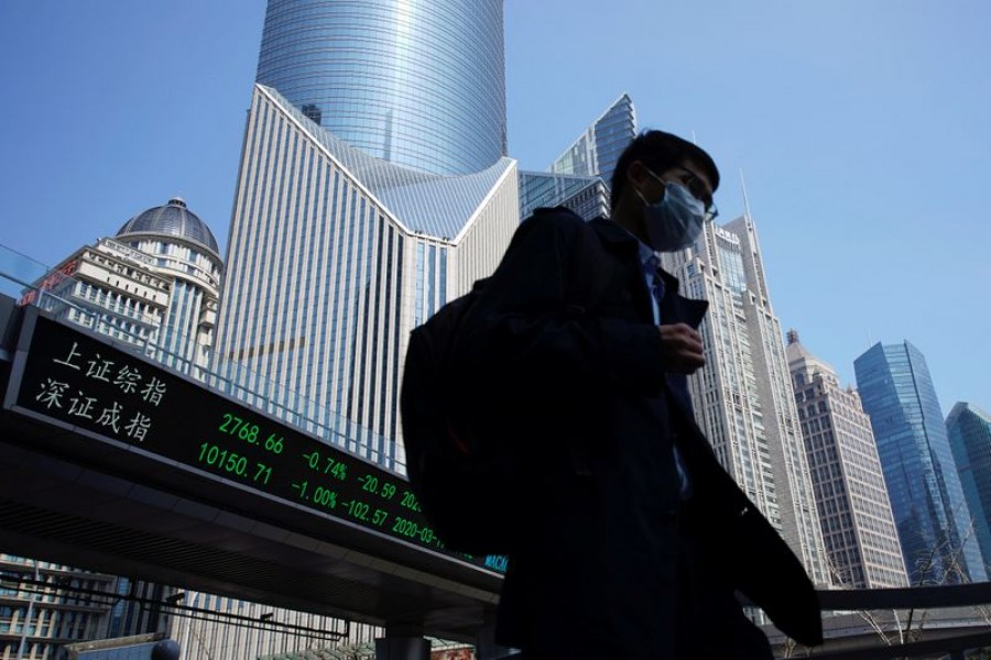 A pedestrian wearing a face mask walks near an overpass with an electronic board showing stock information, following an outbreak of the coronavirus disease (Covid-19), at Lujiazui financial district in Shanghai, China March 17, 2020. REUTERS/Aly Song