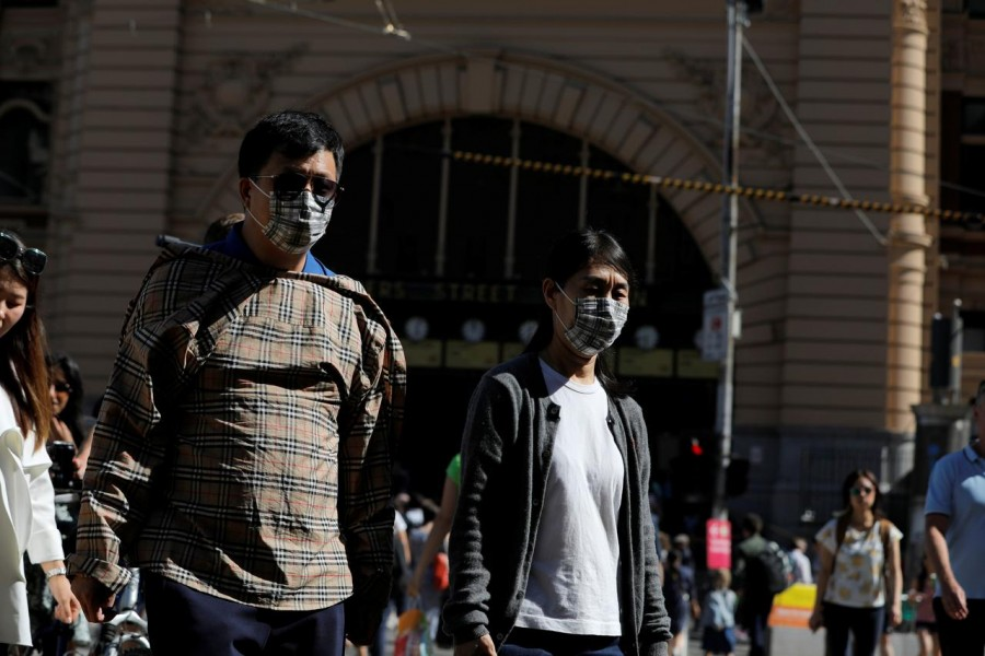 People wearing face masks walk by Flinders Street Station after cases of the coronavirus were confirmed in Melbourne, Victoria, Australia, January 29, 2020. REUTERS/Andrew Kelly