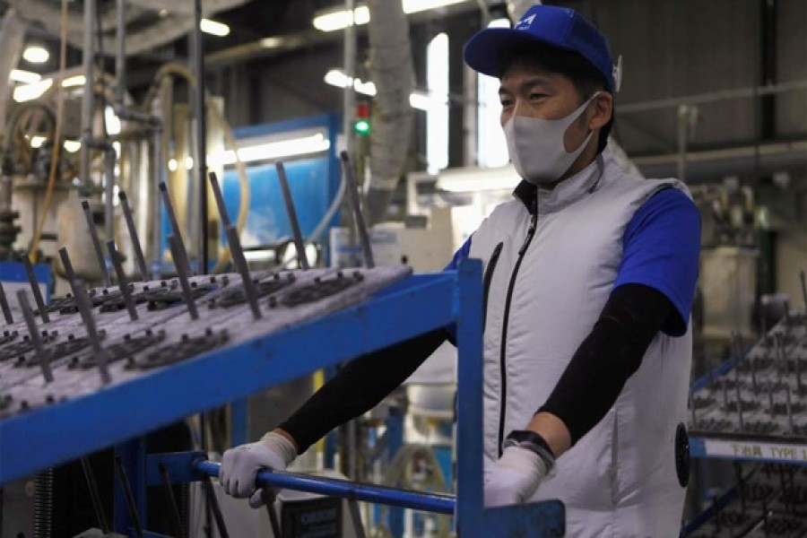 An employee of Marelli?fs factory wearing a protective face mask and a vest equipped with battery-powered fans at the waist, to prevent heatstroke during summer season, is seen amid the coronavirus disease (COVID-19) outbreak, in Ora Town, Gunma Prefecture, Japan Jul 30, 2020. REUTERS An employee of Marelli?fs factory wearing a protective face mask and a vest equipped with battery-powered fans at the waist, to prevent heatstroke during summer season, is seen amid the coronavirus disease (COVID-19) outbreak, in Ora Town, Gunma Prefecture, Japan Jul 30, 2020. REUTERS