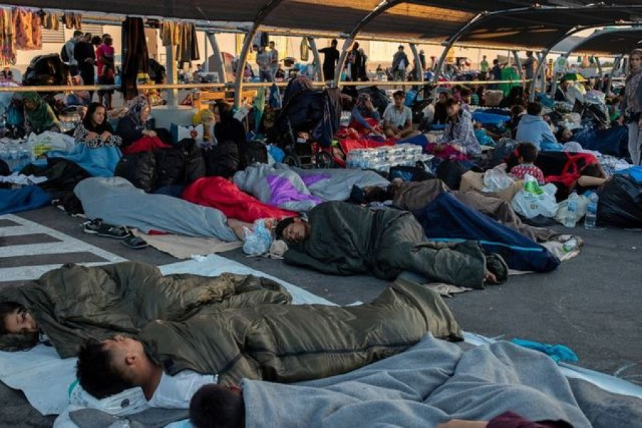 Refugees and migrants sleep at the parking of a supermarket, following a fire at the Moria camp on the island of Lesbos, Greece, September 11, 2020. REUTERS/Alkis Konstantinidis
