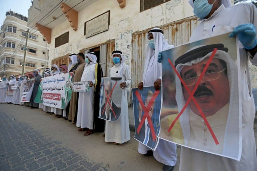 Palestinians hold crossed out posters depicting Bahrain's King Hamad bin Isa Al Khalifa, US President Donald Trump and Israeli Prime Minister Benjamin Netanyahu during a protest against Bahrain's move to normalise relations with Israel, in the central Gaza Strip September 12, 2020 — Reuters