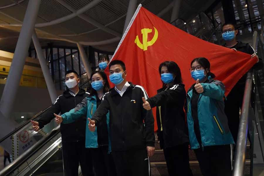 Medical workers from outside Wuhan posing for pictures with a Chinese Communist Party flag at the Wuhan Railway Station before leaving the city in March this year –Reuters file photo